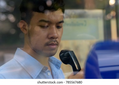 Portrait of young Asian businessman using the payphone outdoors