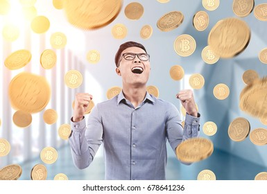 Portrait of a young Asian businessman wearing glasses and a blue shirt and standing in an office under a bitcoin rain.