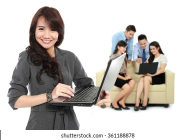 A portrait of a young asian businesswoman, with her team behind holding laptop. isolated in white background