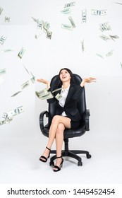 portrait young asian businesswoman is sitting on boss shair with  happily about many flying dollars notes and droping, on white background. copy space