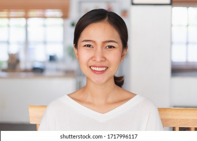 Portrait young Asian businesswoman work at home and virtual video conference meeting with colleagues business people, online working, video call camera view, front view, look at camera
