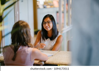 Portrait of a young, Asian Chinese woman in a meeting with a Caucasian woman. She is having a meeting or having an interview and is professionally dressed as she has a discussion at a table indoors.