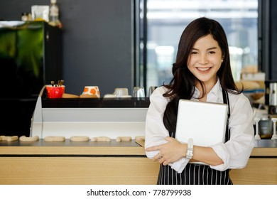Portrait of Young Asian confident barista entrepreneur tanding behind her cafe counter.