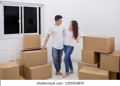 Portrait of young Asian couple standing with a stack of cardboard boxes in the new house