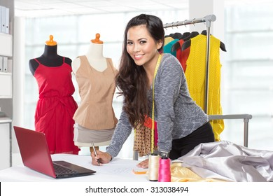 A portrait of a young asian designer woman using a laptop and smiling,clothes hanged as background