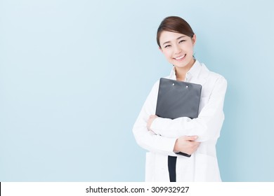 portrait of young asian doctor isolated on blue background