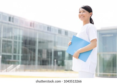 portrait of young asian doctor outside of hospital