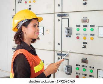 Portrait of a young Asian electric engineering woman is smiling and standing in the energy control room.