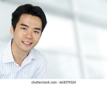 Portrait of young Asian executive in office suit, sitting in front of a modern building