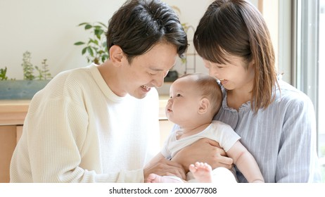 portrait of young asian family with baby relaxing in the living room