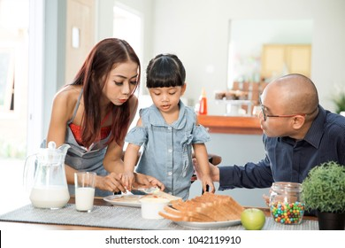 portrait of young asian family having healthy breakfast in the dining room