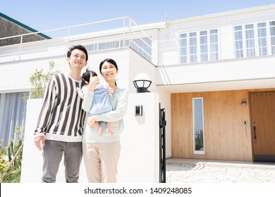 portrait of young asian family standing in the entrance