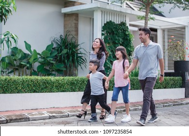 portrait of young asian family in their neighborhood walking around together