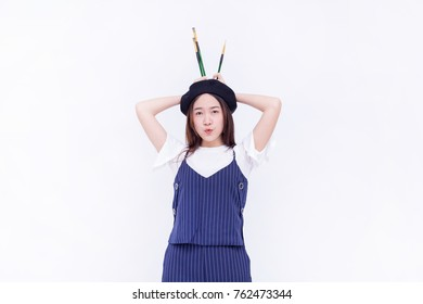 Portrait of young Asian female artist, or pretty girl with Artist hat or pure wool Beret Hat with Artist bib uniform smiling with her paintbrush or artist brush (isolated on white background)