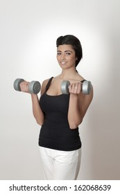 Portrait of young asian female doing exercises with dumbbells