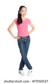 Portrait of young Asian female in pink shirt and jeans with ponytail hair is smiling, full length standing isolated on white background.