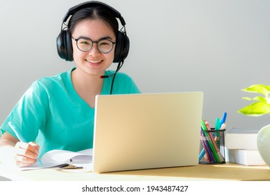 Portrait young Asian female student with headphones glasses smile looking up a note on the book a teenage girl is happy to university internet distance study online class on a laptop computer at home