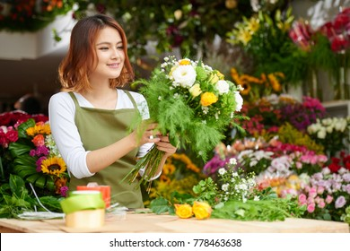 Portrait of young Asian florist wearing apron standing at counter and focused on making bouquet for client, interior of flower shop on background