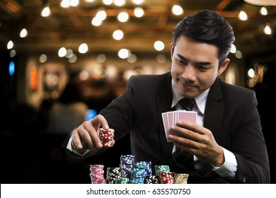 portrait of the young asian gambler is putting bets into the piles of chips, in the left hand holding poker card, on casino background, business casino concept