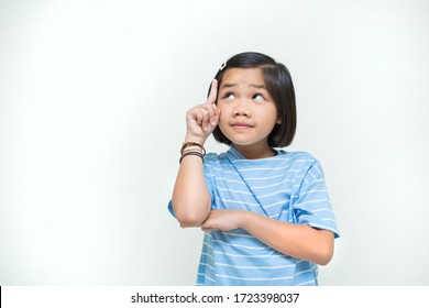 Portrait of young Asian girl kid on white background thinking of new ideas, day dreaming, acting like a smart genius.