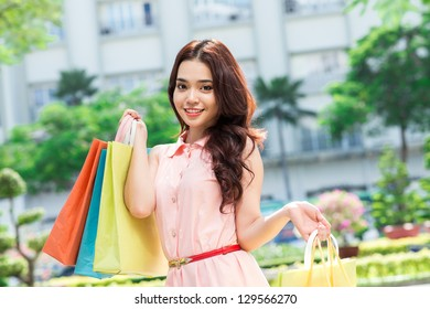 Portrait of a young asian girl with shopping bags outdoors