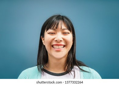 Portrait of young Asian girl smiling at camera - Happy Chinese woman having fun posing against blue background - Teen, trendy, millennial generation and youth people lifestyle