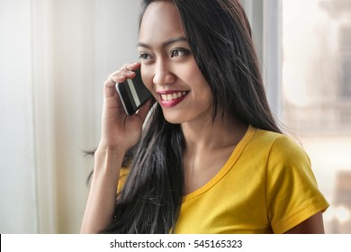 Portrait of a young asian girl talking with someone to the phone