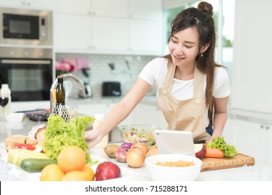 Portrait of young asian girl try to reach the ingredients on the table while cooking salad for her meal