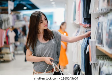 Portrait of a young Asian Japanese woman in casual wear (shorts and comfortable blouse) browsing and shopping for clothes in a clothing store. She is holding a shopping basket filled with clothes.