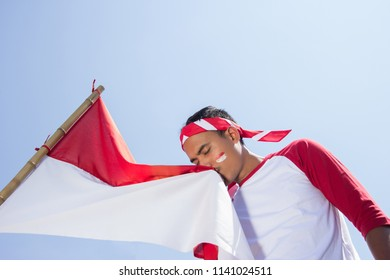 portrait of young asian kissing red and white flag of indonesia under the bright blue sky