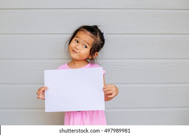 Portrait of a young asian little girl holding a blank sign white paper on wood gray background