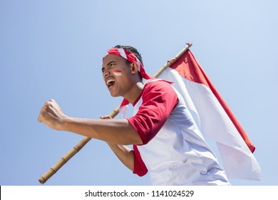 portrait of young asian male holding indonesian flag. patriotic nationalism concept