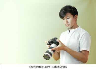 Portrait of young asian male photographer checking captured photos in his digital camera. Isolated man on plain background copy space.