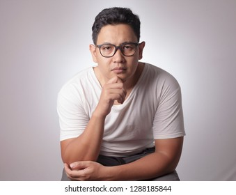 Portrait of young Asian man in casual white shirt staring at camera with suspicious cynical expression