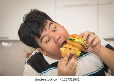 Portrait young Asian man fat, eat hamburger in hand, with a gluttonous glance happily in the house.