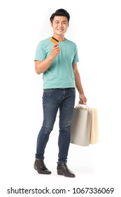 Portrait of young Asian man holding shopping bags and credit card isolated on white