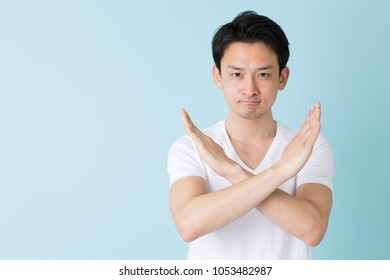 portrait of young asian man isolated on blue background