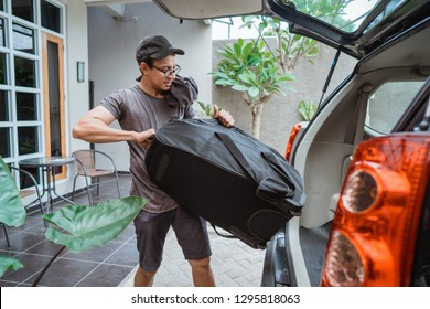 portrait of young asian man lifting a suitcase when go travel and prepare own luggage