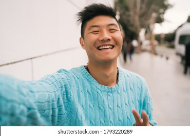 Portrait of young Asian man looking confident and taking a selfie while standing outdoors in the street.