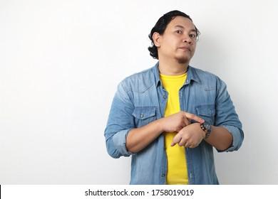 Porträt eines jungen Asienmanns, der auf seine Armbanduhr zeigt, Chefmanager, der vor Zeitkonzept warnen soll