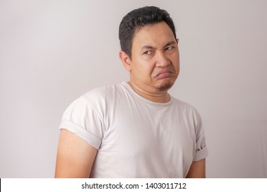 Portrait of young Asian man shows disgusted or displeased expression