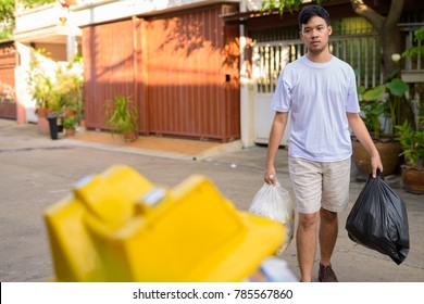 Portrait of young Asian man taking out the garbage at home