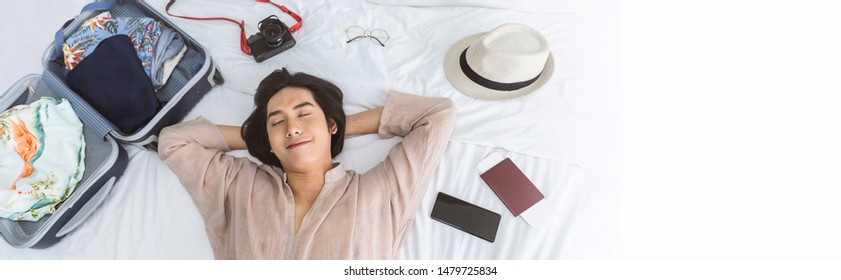 Portrait of young asian man traveler prepare suitcase for holiday vacation. Top overhead view of couple of tourists lying on bed in hotel room. Asian backpacker travel lifestyle concept banner