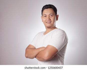 Portrait of young Asian man wearing casual white shirt smiling and shows proud gesture, crossed arm. Close up body portrait