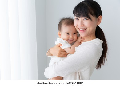 portrait of young asian mother and baby in living room