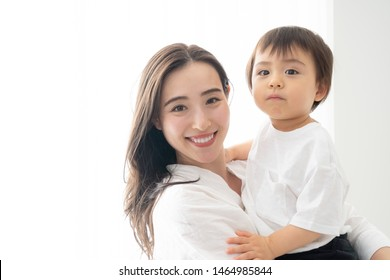 portrait of young asian mother hugging   little baby in living room