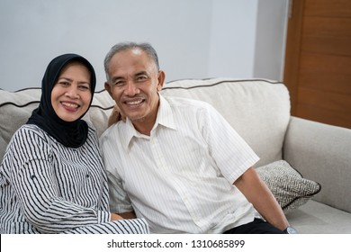 portrait of young asian muslim eldery couple together smiling to camera