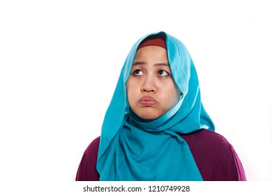 Portrait of young Asian muslim woman showing tired diizzy sluggish gesture, isolated on white