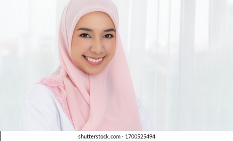 Portrait young asian muslim woman in pink headscarf smile with send kiss. Happy moment concept.