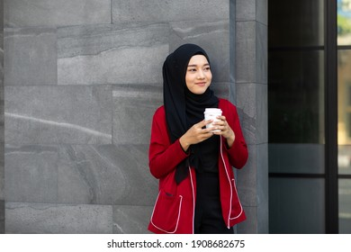 Portrait of young Asian muslim woman wearing hijab head scarf drink coffee and relax time on street in the city